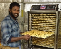Abraham drying apples for home and friends using Taproot's commercial dehydrator.