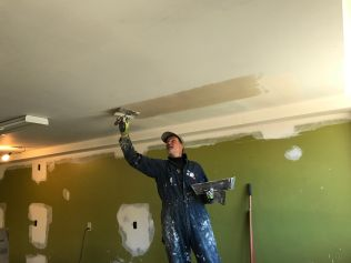 Chris Coiley works on mudding the ceiling.